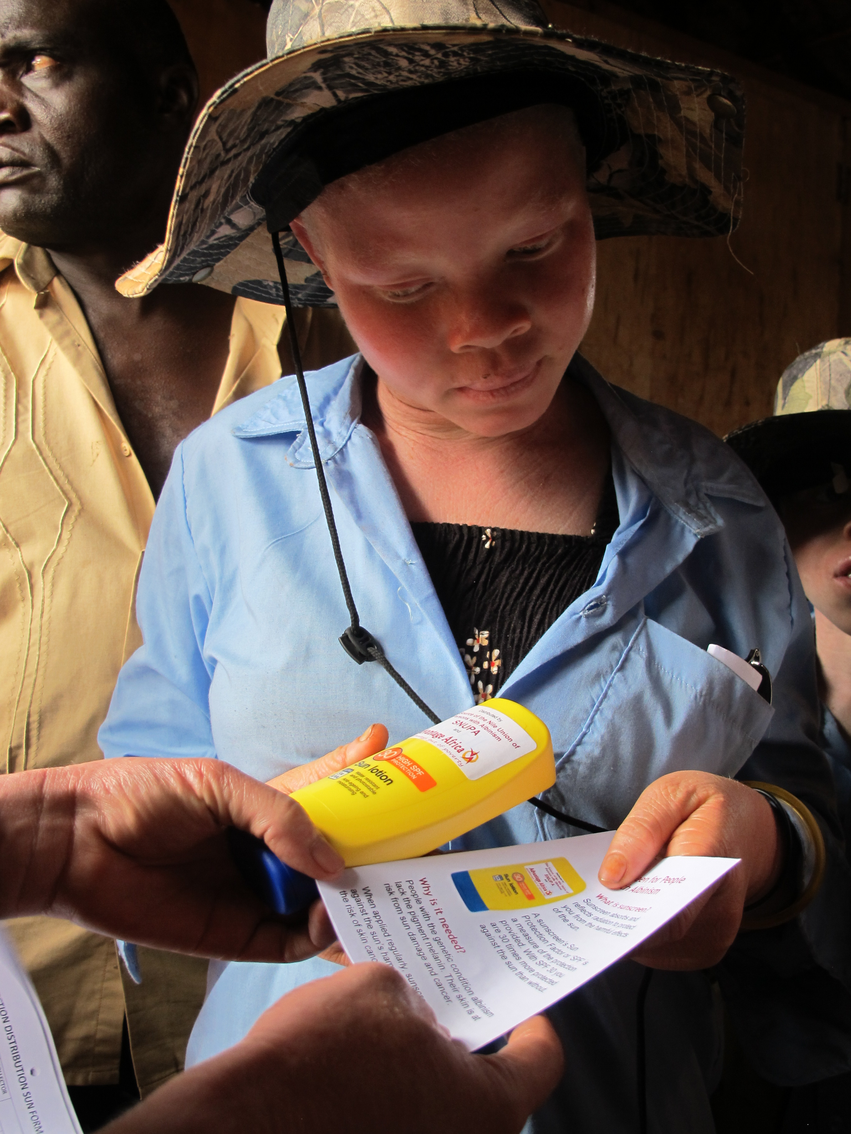 Girl receiving sunscreen and leaflet